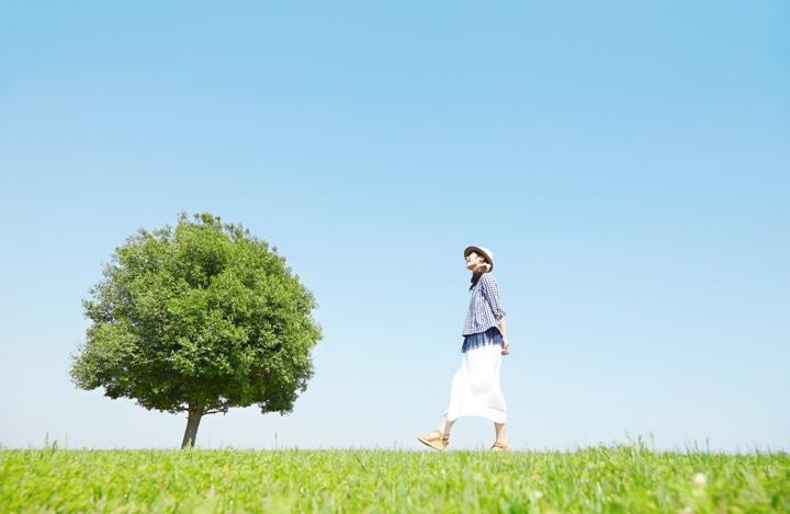 原っぱを歩く女性 画像